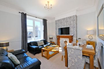 Broomhill self catering apartment lounge showing fireplace and dining table